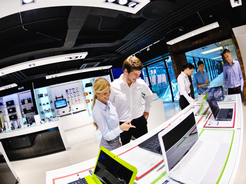 Young couple in consumer electronics store looking at latest laptop, television and photo camera.jpeg